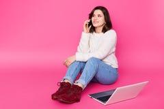La hembra atractiva con sonrisa hermosa se sienta en piso en casa, habla en el teléfono móvil La muchacha hermosa trabaja en líne foto de archivo libre de regalías