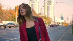 La hembra atractiva joven consigue la situación preocupada en la acera en la ciudad, por el camino, el mecanografiar enfadado en  almacen de metraje de vídeo