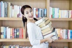 La hembra atractiva trae la pila de libros en biblioteca Imagen de archivo libre de regalías