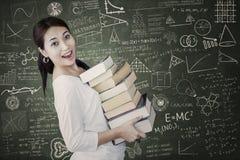 La hembra atractiva trae la pila de libros en clase Imagenes de archivo