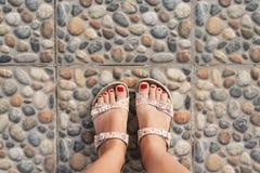 La hembra bronceó las piernas con una pedicura roja en sandalias abiertas en un deco fotografía de archivo libre de regalías