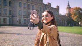La hembra caucásica bonita está teniendo llamada video y está sosteniendo su teléfono en una mano mientras que se coloca fondo al metrajes