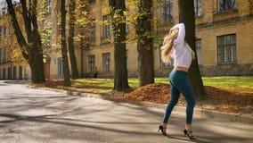 La hembra caucásica impresionante con el pelo rubio largo está bailando Latina en la calle, formación universitaria almacen de metraje de vídeo