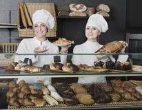 La hembra cocina la demostración y la venta de los pasteles en el café Fotografía de archivo