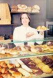 La hembra cocina la demostración y la venta a los pasteles del cliente Imágenes de archivo libres de regalías