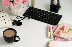 La hembra compone los accesorios, la taza de cofee y el ramo de rosas rosadas en el fondo blanco Endecha plana, escritorio femeni Foto de archivo