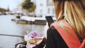La hembra con la bicicleta toma las fotos en el puente del río La señora con el pelo y las flores largos comparte las fotos con l almacen de video
