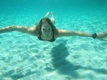 La hembra con los ojos se abre bajo el agua en el océano Imagenes de archivo