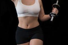 La hembra con una pesa de gimnasia se divierte Fotografía de archivo libre de regalías