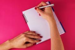 La hembra da el diario personal en fondo rosado imágenes de archivo libres de regalías