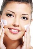 La hembra de la belleza aplica la crema cosmética fotos de archivo libres de regalías