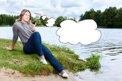 Mujer de pensamiento con el teléfono móvil cerca del agua Imagen de archivo libre de regalías