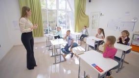 La hembra del profesor obra recíprocamente con el pequeño alumno lindo de los niños en los escritorios durante la lección de la e almacen de video
