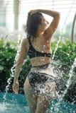 La hembra delgada atractiva en traje de ba?o toma la ducha en piscina entre los arbustos verdes en tejado con el fondo del scape  fotografía de archivo libre de regalías
