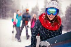 La hembra deportiva sonriente sostiene la snowboard en montañas el invierno imagen de archivo libre de regalías