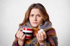 La hembra descontentada adorable siente enferma, bebe té caliente con la frambuesa, pañuelo de los controles como tiene nariz del fotos de archivo libres de regalías