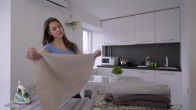 La hembra divertida del ama de casa está planchando las toallas frescas y está engañando alrededor y está cantando metrajes