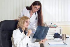 La hembra doctor a X-ray de Consulting About Patient's en sitio de consulta fotografía de archivo libre de regalías