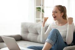 La hembra emocionada se relaja en noticias de la lectura del sofá buenas en línea fotografía de archivo