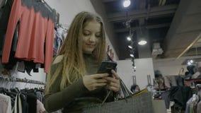 La hembra emocionada sonriente en la tienda que sostiene los panieres recibe los textos de su marido y lo contesta - metrajes