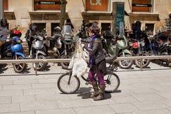 La hembra empuja su bicicleta con los bolsos que hacen compras llenos imagenes de archivo