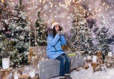 La hembra en abajo chaqueta azul sopla los copos de nieve mientras que se sienta en un s Imágenes de archivo libres de regalías