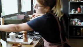 La hembra en delantal prepara la cena en cacerola del wok almacen de metraje de vídeo