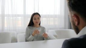 La hembra en el psicólogo habla de problemas, de la conversación de hombres y de mujeres en espacio de oficina,