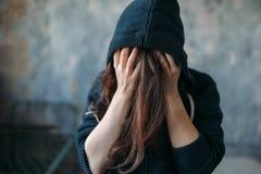 La hembra en una sudadera con capucha lleva a cabo su cabeza imagen de archivo