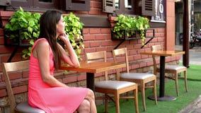 La hembra está esperando alguien en un café en la calle de la reunión, agitando su mano a un amigo, 4k almacen de metraje de vídeo