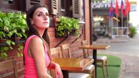 La hembra está esperando alguien en un café en la calle de la reunión, agitando su mano a un amigo, 4k metrajes