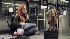 La hembra está esperando vuelo retrasado en el aeropuerto de la noche