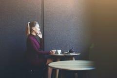 La hembra está llamando vía el teléfono elegante a su amigo mientras que es relajante en cafetería después de día del trabajo Imagen de archivo libre de regalías