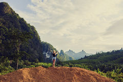 La hembra está tomando la foto con la cámara elegante del teléfono, mientras que se está oponiendo a paisaje de la selva fotos de archivo libres de regalías
