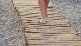 La hembra hermosa bronceó pies que caminaba a lo largo de la calzada de madera en la playa la muchacha camina en la playa almacen de metraje de vídeo