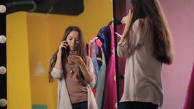 La hembra hermosa joven está hablando en el teléfono celular que se coloca delante del espejo metrajes