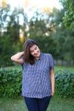 La hembra hermosa que mira sonrisa ausente, linda y corrige el pelo en p Foto de archivo