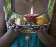 La hembra india joven se vistió en la ropa tradicional que llevaba los dulces de Diwali del indio