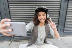La hembra joven alegre del inconformista está descansando sobre la calle Imagen de archivo libre de regalías