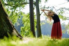 La hembra joven atractiva en falda roja está practicando yoga y está haciendo asana por la mañana Imagen de archivo libre de regalías