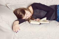 La hembra joven atractiva está durmiendo en el sofá con el libro Foto de archivo libre de regalías
