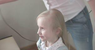 La hembra joven atractiva hace un peinado del ` s de la niña metrajes