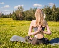 La hembra joven con los brazos abiertos y el pelo rubio largo que se sientan cómodamente y se relaja en actitud de la yoga en nat imagen de archivo libre de regalías