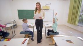 La hembra joven del educador distribuye las hojas de papel blancas al control del conocimiento de alumnos en los escritorios dura metrajes