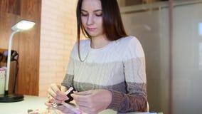 La hembra joven elige el color y la textura de clavos en el salón de belleza profesional de la manicura, resbalador almacen de metraje de vídeo