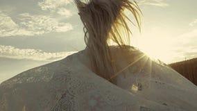 La hembra joven en estilo del boho está corriendo en la puesta del sol Muchacha atractiva en blanco almacen de metraje de vídeo