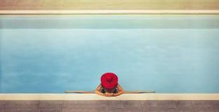 La hembra joven en un sombrero se sienta en una guita en la piscina Fotografía de archivo
