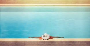 La hembra joven en un sombrero se sienta en una guita en la piscina Foto de archivo libre de regalías