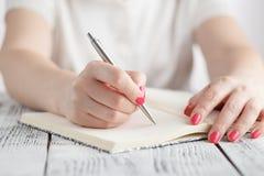 La hembra joven es notas y hojas de operación (planning) de la escritura su horario Fotos de archivo libres de regalías
