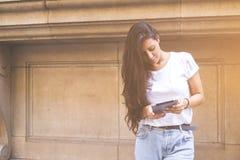 La hembra joven está buscando la información en Internet vía la tableta digital Imágenes de archivo libres de regalías